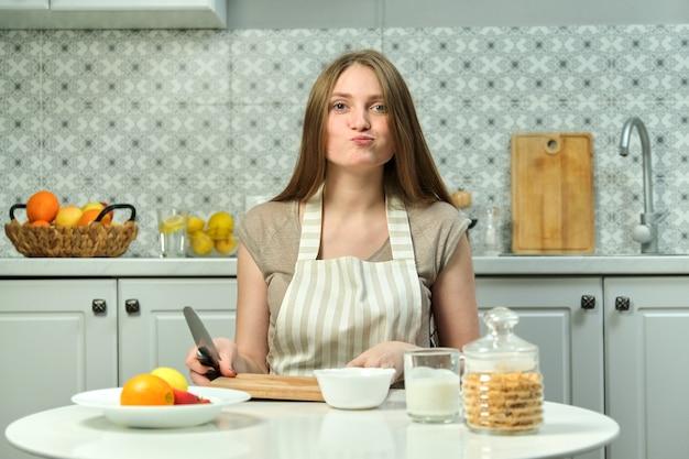 Jovem e linda mulher sentada à mesa na cozinha com uma tábua de cortar faca de produtos de frutas