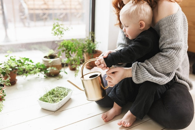 Jovem e linda mulher sentada no chão com seu filho segurando um regador nas mãos com plantas verdes perto de uma grande janela