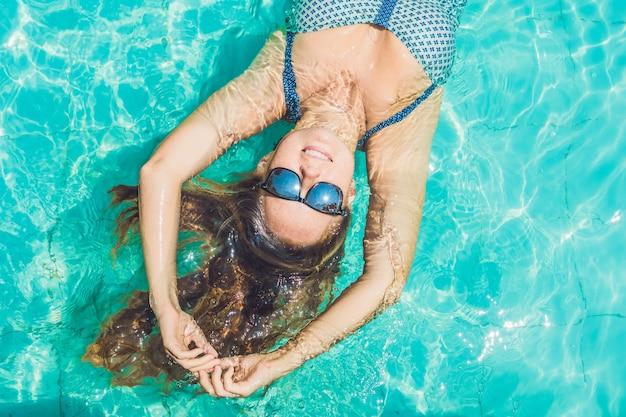 Jovem e linda mulher sorridente de biquíni deitada na superfície da piscina com água azul-turquesa