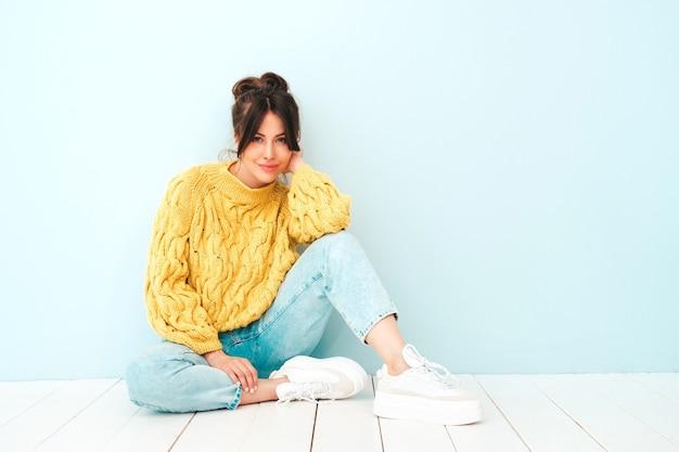Jovem e linda mulher sorridente em jeans e suéter amarelo moderno de verão