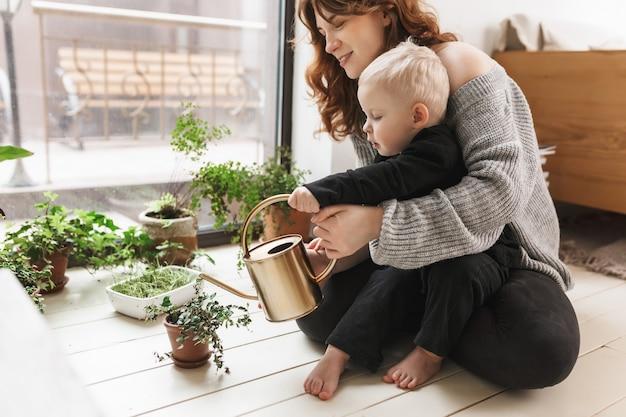 Jovem e linda mulher sorridente sentada no chão com seu filho segurando um regador nas mãos com plantas verdes perto de uma grande janela