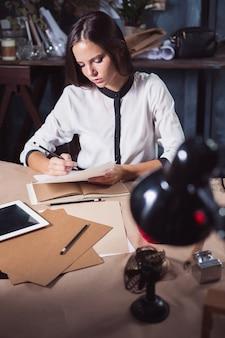 Jovem e linda mulher trabalhando com uma xícara de café