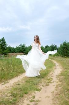 Jovem e linda noiva com vestido de noiva branco girando