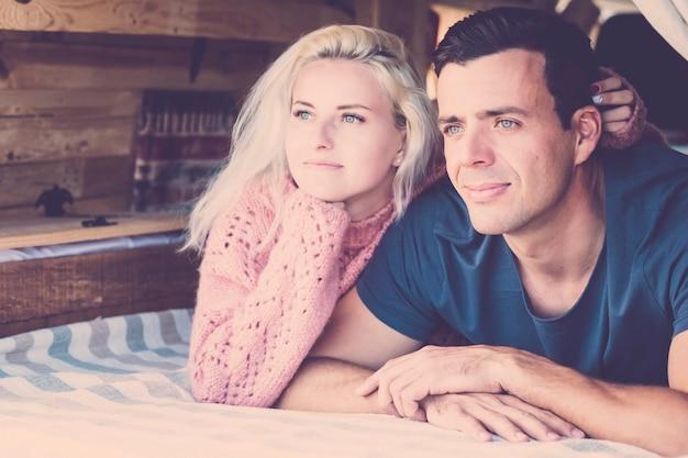 Jovem e lindo casal milenar olhando para fora se deitando em uma pequena van de campista vintage durante férias alternativas, curtindo a natureza e o conceito de viagens - ambos olhos azuis