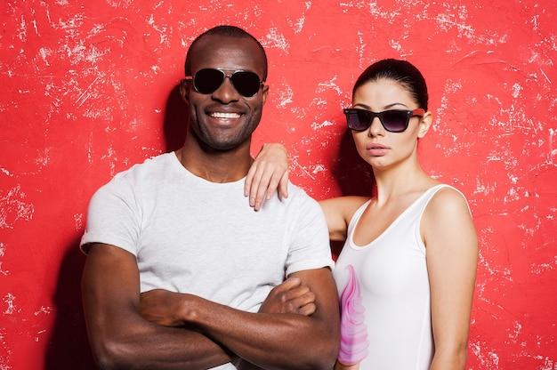 Jovem e livre. lindo casal jovem de raça mista em óculos de sol, juntos contra um fundo vermelho e sorrindo