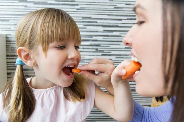 Jovem e menina comendo cenouras na cozinha