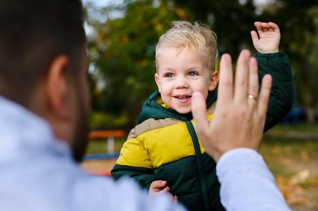 Jovem e menino com as palmas das mãos levantadas