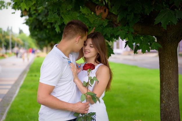 Jovem e mulher abraçando num encontro em pé debaixo de uma árvore