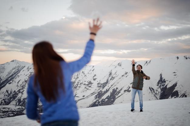 Jovem e mulher acenando as mãos nas montanhas