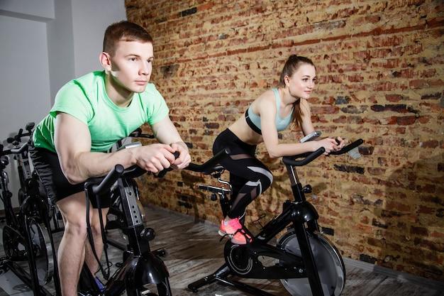 Jovem e mulher, andar de bicicleta no ginásio, exercitar as pernas fazendo exercício cardio cardio bicicletas