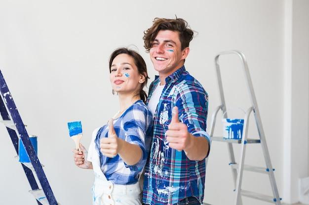 Jovem e mulher apaixonada e pintando a parede, mostrando os polegares.