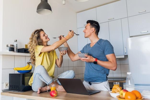 Jovem e mulher apaixonada se divertindo saudável café da manhã na cozinha pela manhã