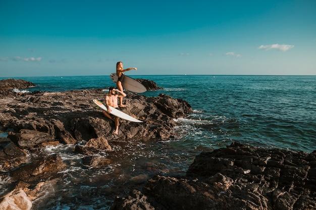Jovem e mulher apontando para o lado com pranchas de surf na rocha perto do mar