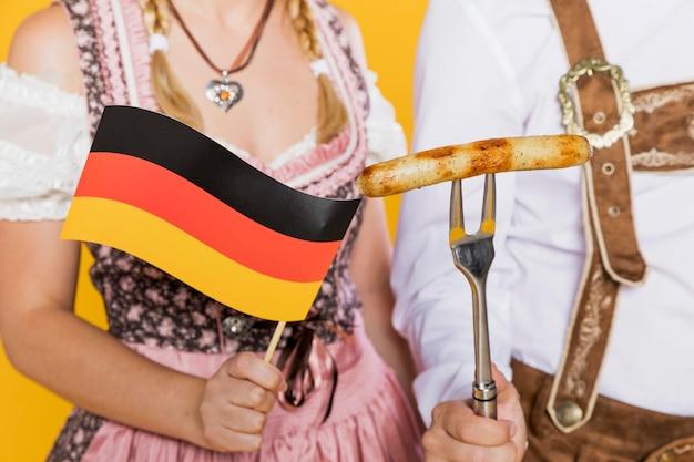 Jovem e mulher bandeira alemã e salsicha grelhada