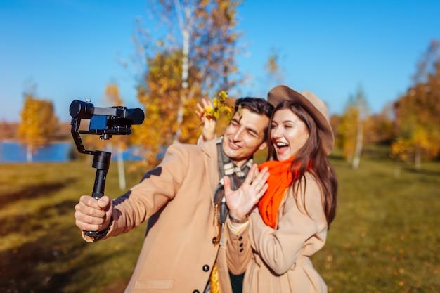 Jovem e mulher blogueiros filmando filmagens usando steadicam