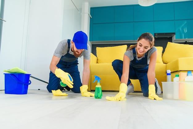 Jovem e mulher bonita são trabalhadores do serviço de limpeza, pulverizando detergentes e limpando o chão com panos
