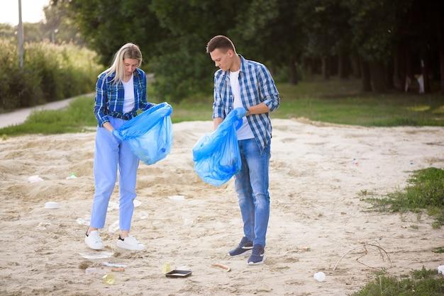 Jovem e mulher catando lixo ao ar livre.