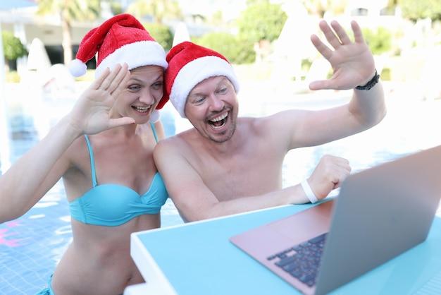 Jovem e mulher com chapéu de papai noel nadando na piscina e acenando para a tela do laptop