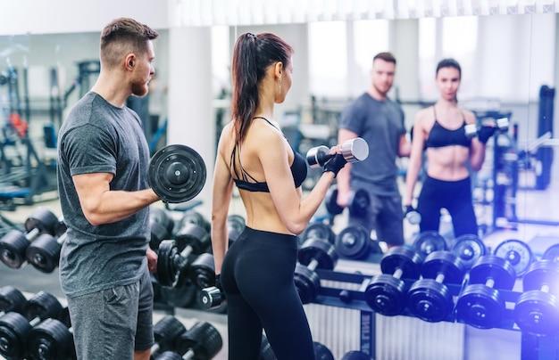 Jovem e mulher com halteres flexionando os músculos na academia