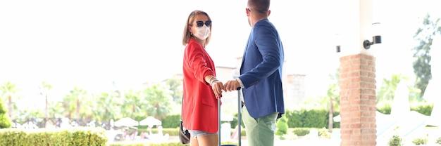 Jovem e mulher com máscaras médicas protetoras em pé com uma mala perto do hotel