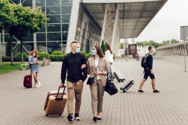 Jovem e mulher com máscaras protetoras com uma mala vão para o aeroporto
