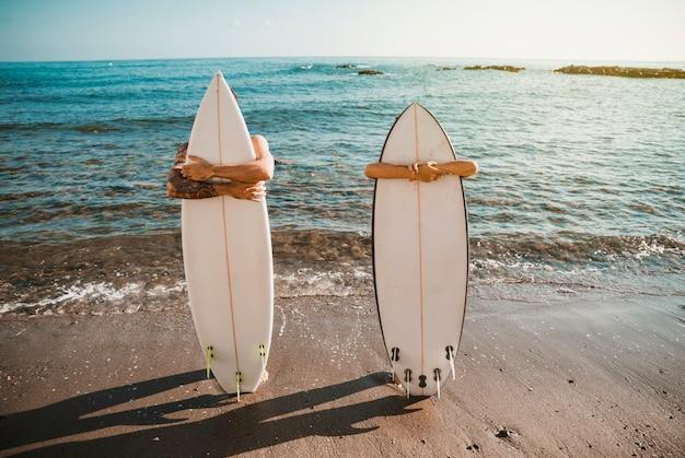 Jovem e mulher com pranchas de surf na costa perto da água