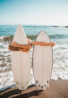 Jovem e mulher com pranchas de surf na costa perto do mar