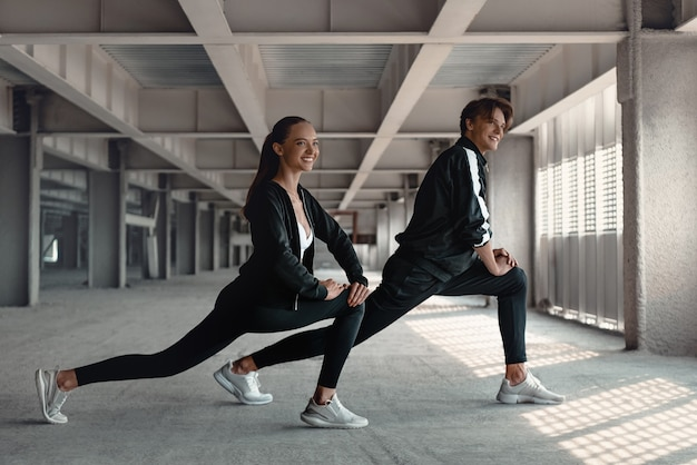 Jovem e mulher com roupas esportivas estão fazendo exercícios de aquecimento no estacionamento perto do estádio. alongamento de mãos e pernas