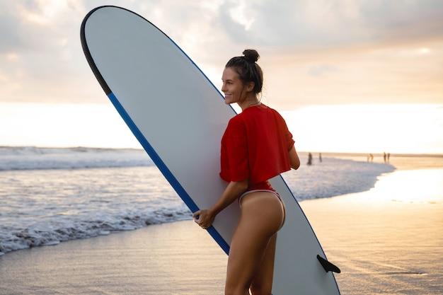 Jovem e mulher com um longboard durante a sessão de surf na praia