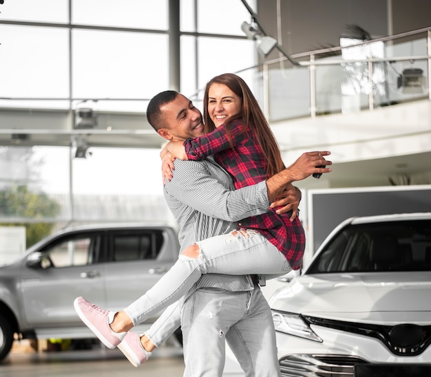 Jovem e mulher comemoram carro novo