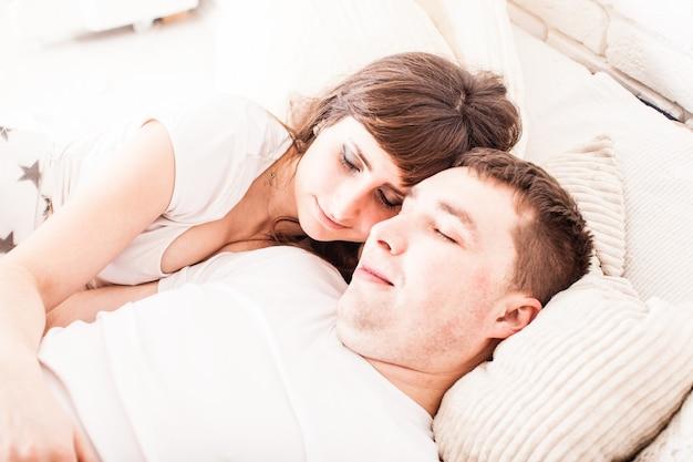 Jovem e mulher de camiseta branca dormindo na cama, abraçando-se
