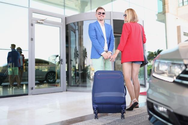 Jovem e mulher de óculos escuros em pé com uma mala perto da entrada do hotel