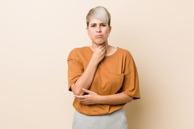 Jovem e mulher de tamanho com cabelo curto sofre dor na garganta devido a um vírus ou infecção.
