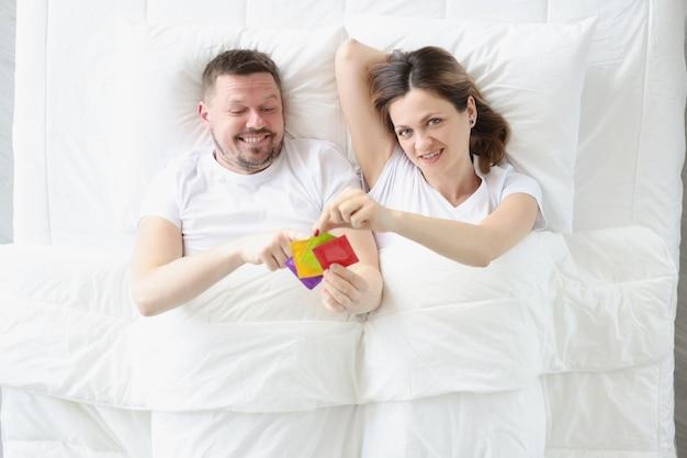 Jovem e mulher deitada na cama segurando muitos preservativos, vista superior, conceito de planejamento de gravidez