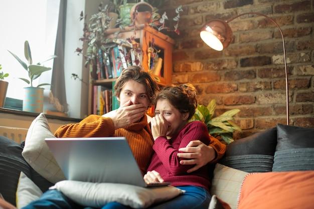 Jovem e mulher deitados no sofá, assistindo a um filme de terror no laptop