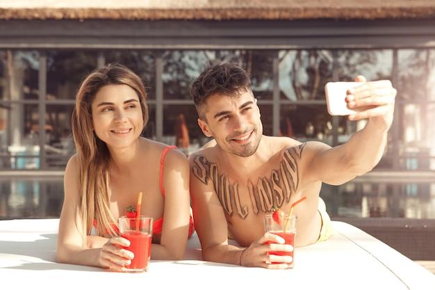 Jovem e mulher descansam juntos perto da piscina tirando fotos