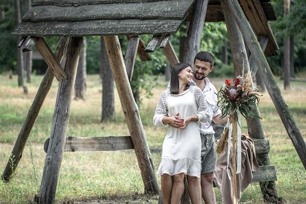 Jovem e mulher elegantemente vestida, abraçando-se na floresta com um buquê de flores exóticas, romance no casamento.