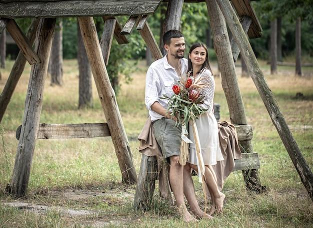 Jovem e mulher elegantemente vestida, com um buquê de flores exóticas, em um encontro na floresta.