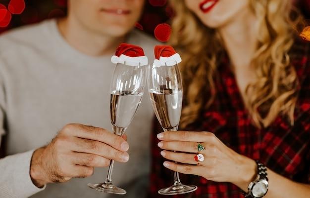 Jovem e mulher em anéis de natal segurando copos de champanhe com decoração de papai noel nele.