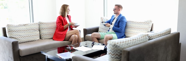 Jovem e mulher em roupas da moda com xícaras de chá no quarto do hotel