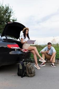 Jovem e mulher fazendo uma pausa na estrada