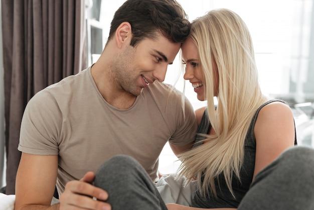 Jovem e mulher flertando e abraçando na cama
