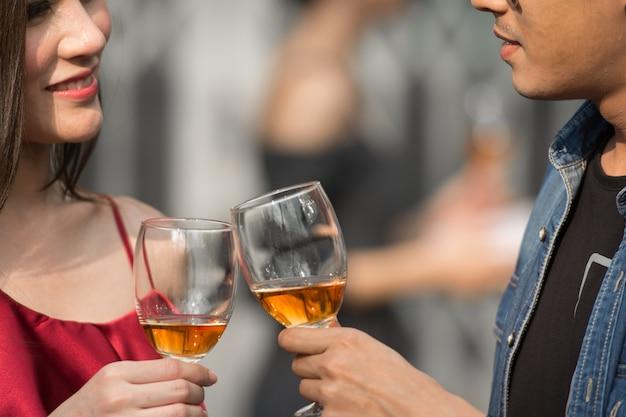 Jovem e mulher na data no restaurante em pé segurando copos de álcool e olhando uns aos outros.