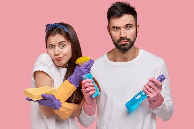 Jovem e mulher posando com produtos de limpeza