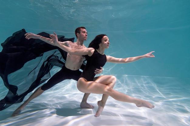 Jovem e mulher posando juntos submersos