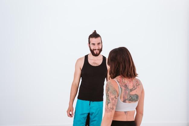 Jovem e mulher praticando ioga esporte na academia