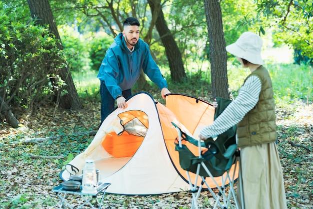 Jovem e mulher preparando barracas para acampar na floresta
