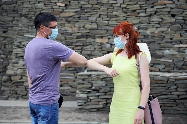 Jovem e mulher se encontraram ao ar livre e cumprimentando cotovelos