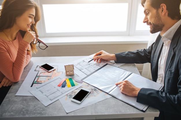 Jovem e mulher se sentam na frente do outro e olham para a planta do apartamento. cara apontar com caneta. concentrado no trabalho. luz do dia.