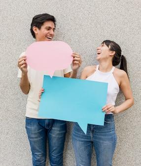 Jovem e mulher segurando balões de fala